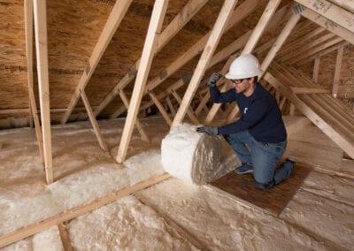 Austin Company | worker installing white fiberglass in attic of home