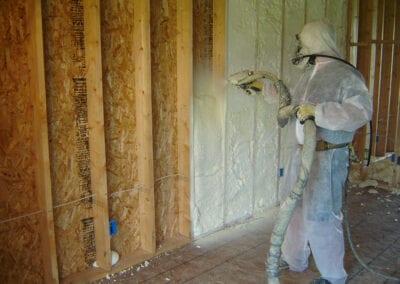 Austin Company | worker in protective gear installing spray foam insulation